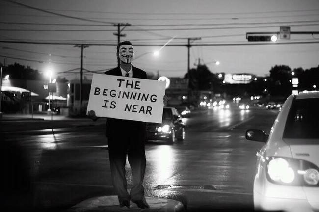 Anonymous standing in traffic with a sign that reads, the beginning is near.