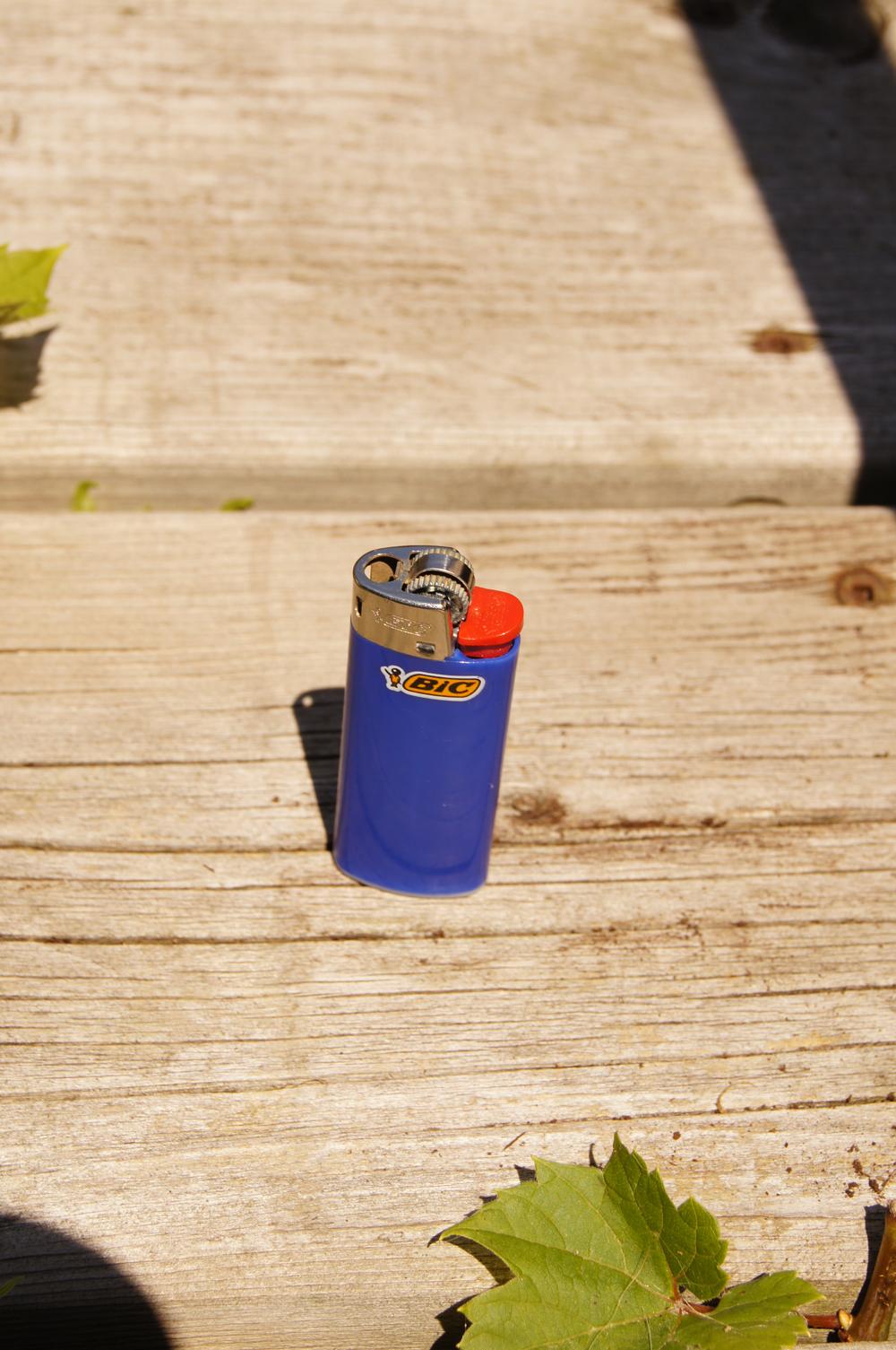 Blue BIC lighter on a wood board