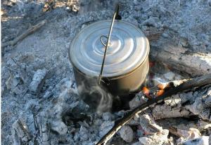 A pot of boiling water on top of a camp fire.