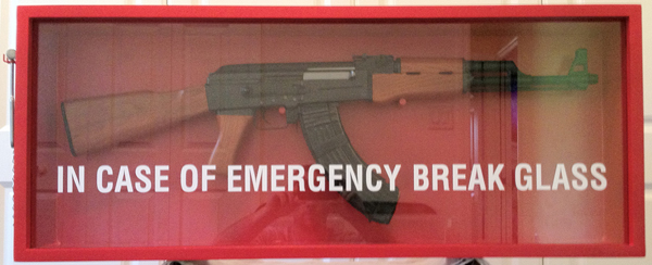 An ak-47 assault rifle in a glass case with the words