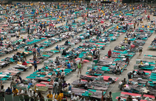 A evacuation shelter with cots and people.