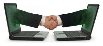 Two laptops with hands emerging from then to form a partnership and a business deal.