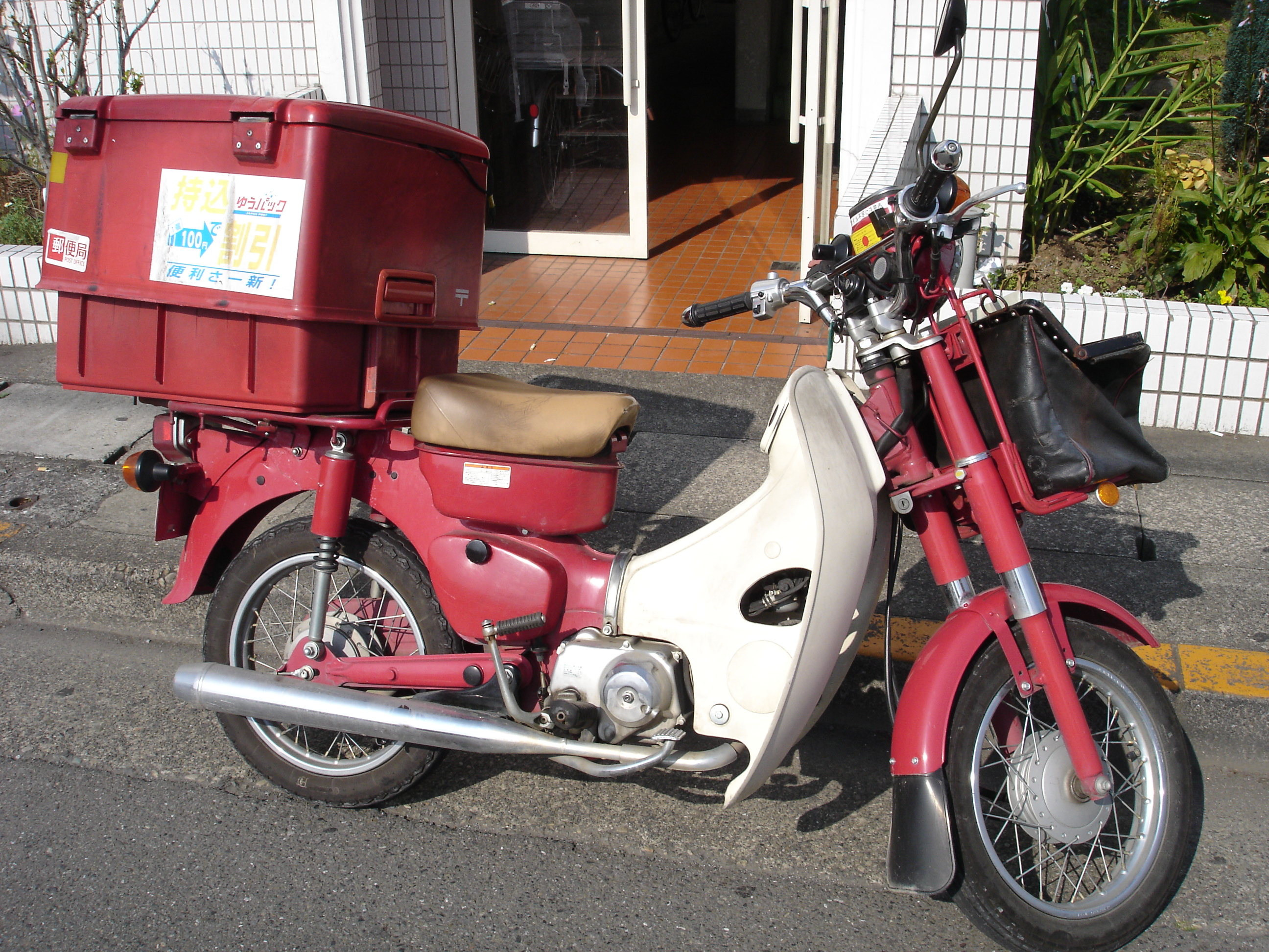 A small motor bike with a large compartment on the back.