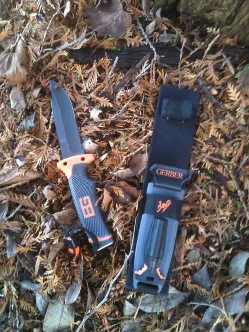 Bear Grylls survival knife with sheath in leaves